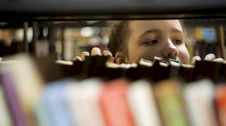 скрывать : Girl looks out from behind the books. Стоковые видеозаписи