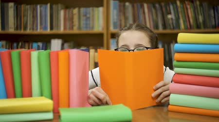 скрывать : Little girl in big glasses hides behind a book, reads a book. Стоковые видеозаписи
