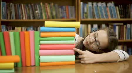 kaczka : A girl with glasses counts how many books.