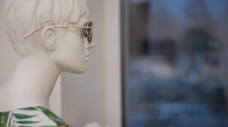têxteis : Mannequin in glasses in the store looks at the evening city
