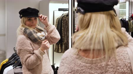 denemek : Pretty girl tries on a hat in an expensive store. Girl posing near the mirror.
