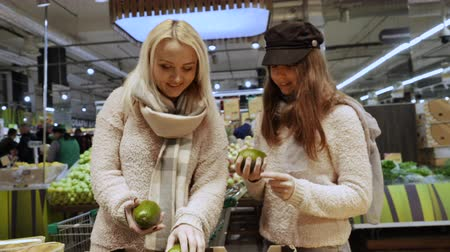 latino americana : Mom buys healthy food with her daughter in the supermarket, choose avocado
