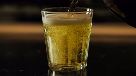 občerstvení : Beer is poured from the top into the glass, forming a foam