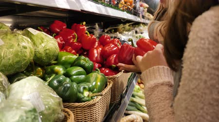 afdeling : A woman in a supermarket on a vegetable shelf, buys vegetables and fruits. Man chooses Bulgarian pepper .Slow motion Stockvideo