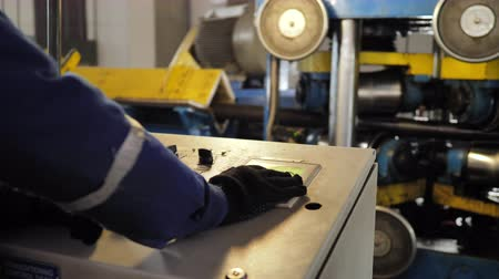 duwen : Worker turning on an industrial machine. Operating pressure switch on the control panel of an industrial machine and switched on at the factory