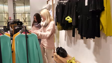 afdeling : Woman and daughter choose clothes in the mall, fashionable womens clothing store