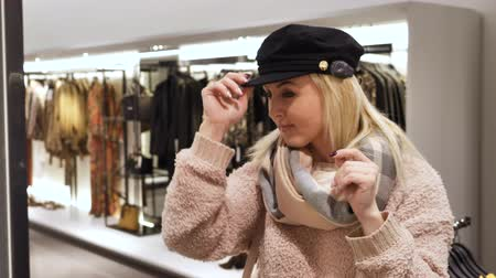 long hair : Woman posing in a new hat in front of a mirror in the store, trying on a hat