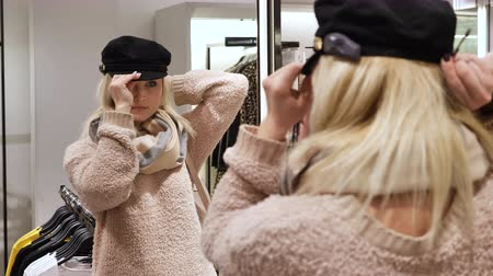 níveis : Woman blonde measures the headgear in the store in front of the mirror
