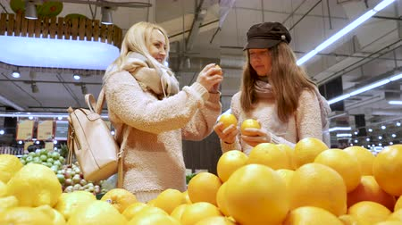 laranjas : Mom and daughter have fun with oranges, choose oranges in the store
