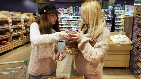 bazar : Mom and daughter buy cookies in the supermarket, pastries in boxes