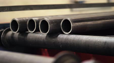 rozsdamentes : Pipe factory. Metal pipes on the conveyor line. Pipe production line in a factory. Stock mozgókép