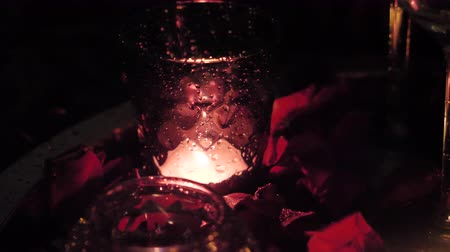 invite : A glass with a candle around rose petals. Romantic Settings