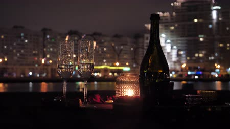 desfocagem : A bottle of champagne with glasses on the background of the night city, a date for a couple in love