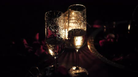 dois objetos : Glasses with champagne near rose petals and candles