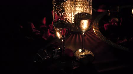 szenteste : Romantic luxury evening with champagne setting with two glasses. rose petails and candles. Champagne for romantic celebrations or New Year party and enjoy for special moments. Bokeh background.