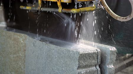 taş işçiliği : Bridge saw machines cutting granite block in slow motion