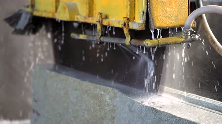 taş işçiliği : A cutting machine prepares slabs of marble and granite. Water and marble debris fly out in slow motion.