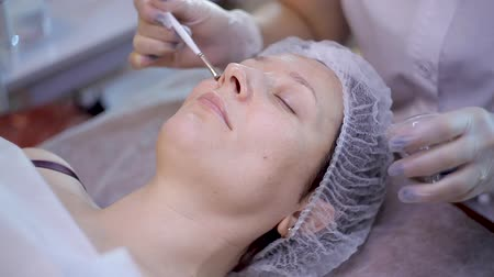 procedimento : Cleansing peeling in the beauty salon. Cosmetic treatment of face. Aesthetic cosmetology. Stock Footage