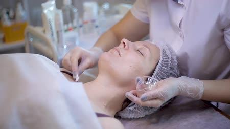 procedimento : Beauty concept. Young female client gets beauty facial procedure. face renovation. Beautician uses cotton bud to cover face skin with beauty mask