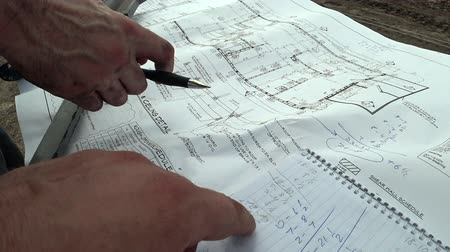 inspektor : An architect and a construction engineer check the building plan for a successful construction, check the exact dimensions of the drawing and write in a notebook, the team discusses the building plan.