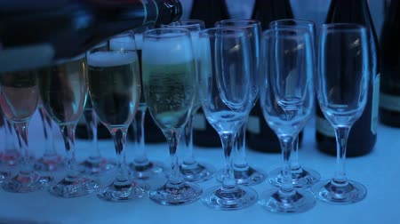 porce : A waiter pours champagne into glasses at a club party. Glasses with champagne on the table are illuminated with different colors of light music. Close-up of glasses