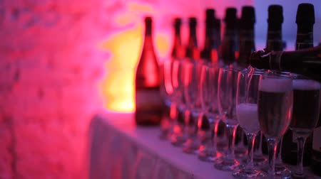 champagne bottles : Champagne glasses stand in a row on the table, highlighted with multi-colored light at the party. In the glasses poured champagne. Preglushonny light in the room. Holiday atmosphere in the club