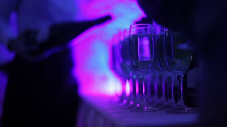 официант : The waiter pours champagne into glasses at the celebration. People at a festive event take glasses of champagne from the table. Color lights party. Subdued light, night club atmosphere