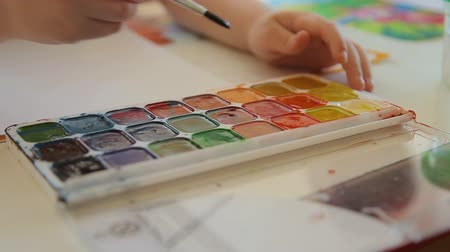 paletta : A child with a brush to paint selects the color of the paint. Set of watercolor paints of different colors. The boy takes the orange paint with a brush. Artists palette, close-up. Drawing tools.