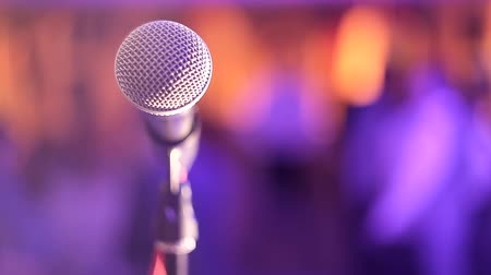 speaker : The microphone on the stand is on the stage, the microphone is close up against the background of the hall. Point of view of the singer. Microphone on an abstract blurred color background.