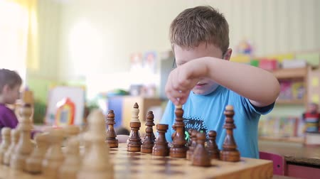 ладья : A boy with glasses plays chess. He is sitting at the table playing and smiling emotionally. Rearranges pieces on a chessboard. He wants to checkmate and win.