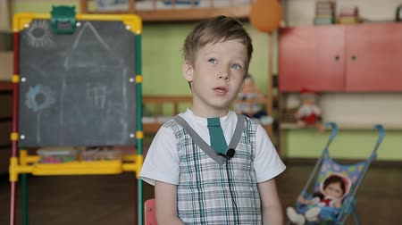 tablica : A 6 year old boy sits on a chair with a lapel microphone on his clothes and answers questions thoughtfully. The boy gives an interview in an educational envy against the background of a blackboard.