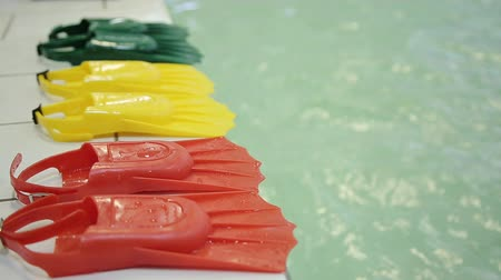 activities : Diving fins in three different colors at the edge of the pool. Green yellow red color. Fins made of rubber and plasmass for swimming on a background of water. Stock Footage