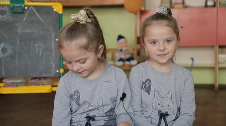 tablica : Twin girls sitting on a chair answers questions. Girls give interviews in a classroom against the background of the blackboard. Themes sister siblings twins affection Wideo