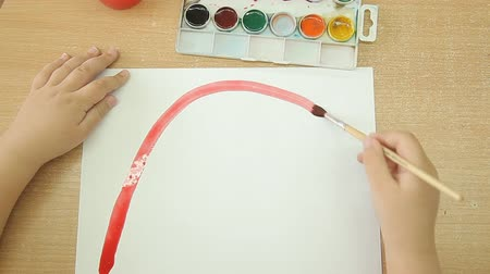 çizmek : The child holds a brush in his right hand and draws a rainbow on a white sheet of paper. Red line of paint on a sheet of white paper Stok Video