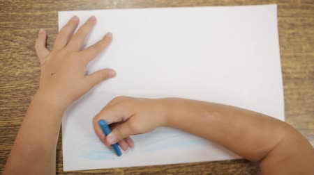 ponta : Girl draws with blue chalk for drawing makes an artistic drawing of the ocean or sea on a white sheet. Hand of a girl with a chalk for drawing close-up. Childs drawing Stock Footage