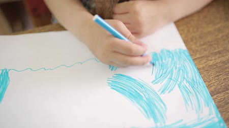 ponta : Girl draws with a blue felt-tip pen makes an artistic drawing of the ocean or sea on a white sheet. Hand of a girl with felt-tip pen close-up. Childs drawing