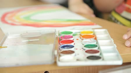 passatempo : The child draws blue paint on a brush for painting. The artist s childrens hand draws paint on the brush. Children draw rainbows in an educational institution. Childs hand with a brush closeup. Stock Footage