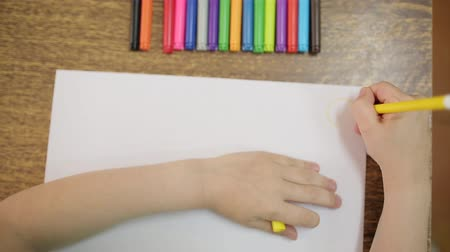 ponta : The child draws with a yellow felt-tip pen on a white sheet of paper. Colored markers on the table. Childs hand with felt-tip pen for drawing close-up. The boy draws a yellow sun.