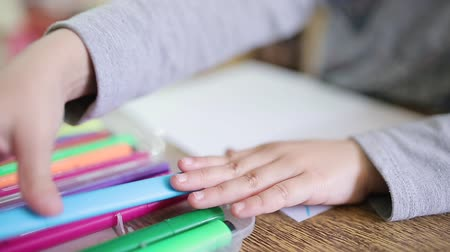 fotografando : A girl puts a felt-tip pen in a box after drawing. The child puts the felt-tip pen in a box with multi-colored felt-tip pens. Childrens drawing. Children draw in class at an educational institution.