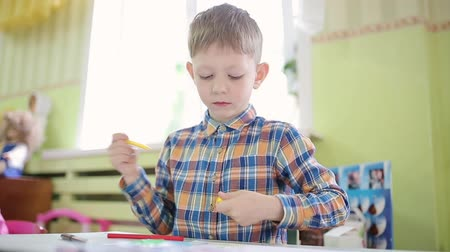 ponta : A boy in a plaid shirt draws with a yellow felt-tip pen. The student performs the task in a preschool. Preschooler child draws with felt-tip pen.