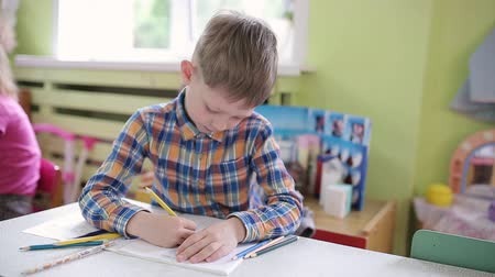шесть : School Preparation Preschool. 6 years old boy in a class at a school desk performs an assignment in a notebook.