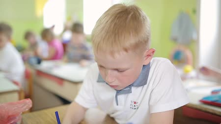 freckles : A red-haired boy with freckles draws a drawing on a white sheet while sitting at a table in kindergarten. 6 year old red-haired child is engaged in preschool education
