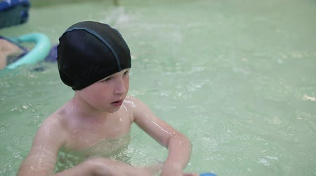 plavec : The boy learns to swim in the pool. 6 year old boy swims in an indoor pool in kindergarten. Swimming training for children