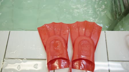 costumi da bagno : Fins for swimming. Red flippers lie on the edge of the pool against the background of water. Baby flippers for swimming