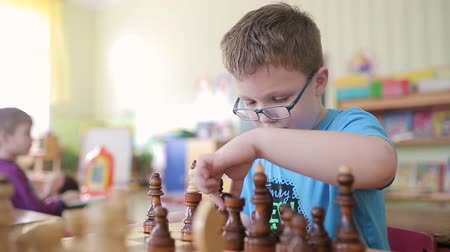 королева : A boy with glasses plays chess. He is sitting at the table, playing a board game. Rearrange pieces on a chessboard. He wants to checkmate and win.