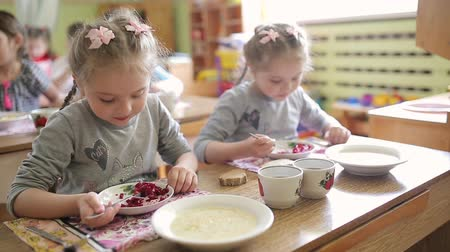 saŁata : Twin girls eating salad while sitting at a table in kindergarten. Eating in preschool envy. Healthy baby food Wideo