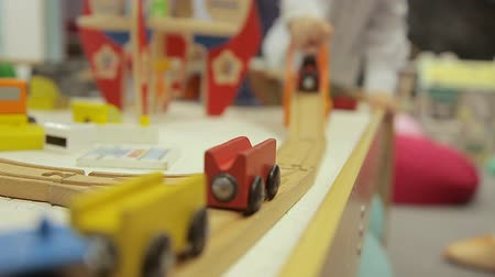 miniatűr : A boy is playing with a childrens train. A boy plays on the railway. Childs hand holds a wooden toy train. A child plays with a childrens model of the railway. Stock mozgókép