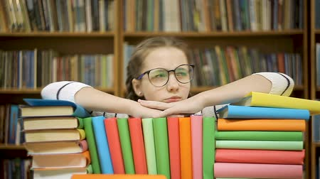 시력 : Girl takes off glasses after reading a book. A girl lies on books in the library. 무비클립