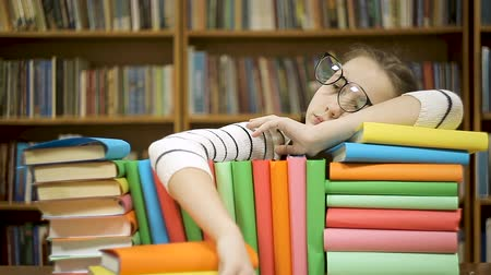 livros : Portrait of a thinking girl got a new idea when planning. Girl with books in the library comes up with a new idea. Stock Footage