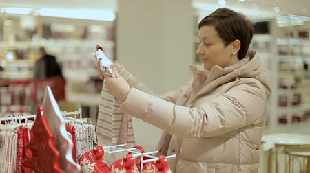 покупатель : Girl chooses Christmas presents. Woman chooses holiday Christmas presents in the mall.
